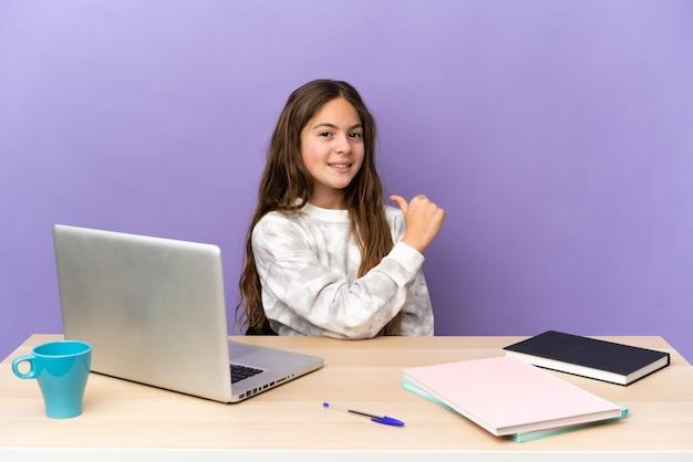 Маленькая студентка на рабочем месте с ноутбуком, изолированным на фиолетовом фоне, гордая и самодовольная
