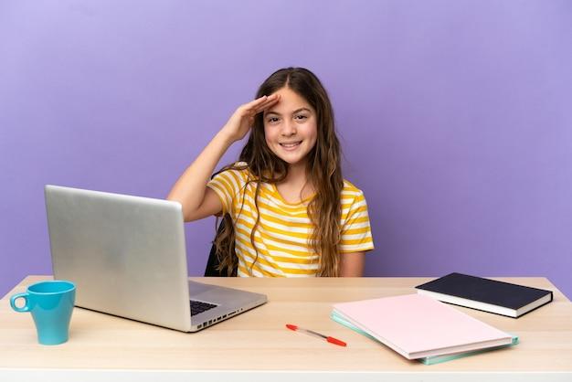 Маленькая студентка на рабочем месте с ноутбуком, изолированным на фиолетовом фоне, салютуя рукой с счастливым выражением лица