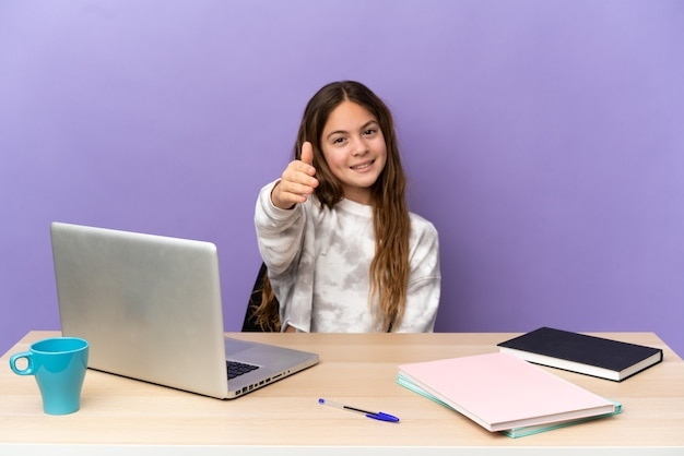 Маленькая студентка на рабочем месте с ноутбуком, изолированным на фиолетовом фоне, пожимая руку для заключения хорошей сделки