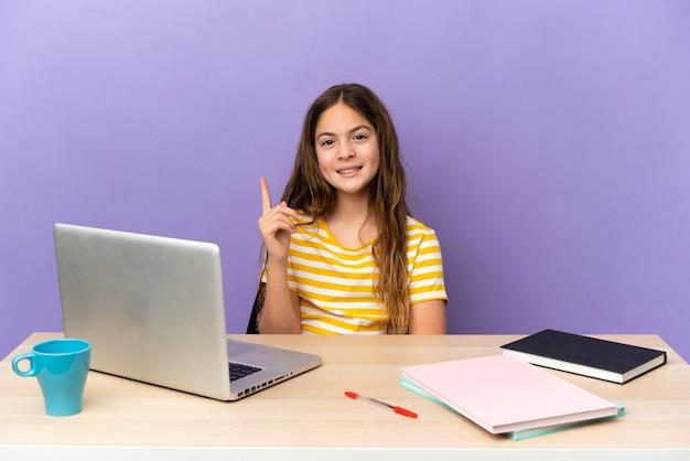 Маленькая студентка на рабочем месте с ноутбуком, изолированным на фиолетовом фоне, показывает и поднимает палец в знак лучших