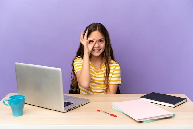 Маленькая девочка-студент на рабочем месте с ноутбуком, изолированным на фиолетовом фоне, показывая пальцами знак ок