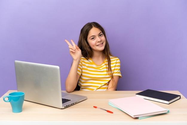 Маленькая студентка на рабочем месте с ноутбуком, изолированным на фиолетовом фоне, улыбается и показывает знак победы