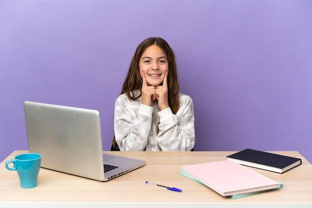 Маленькая девочка-студент на рабочем месте с ноутбуком, изолированным на фиолетовом фоне, улыбаясь счастливым и приятным выражением лица