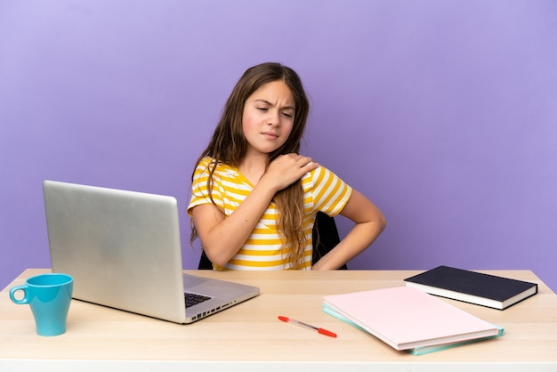 Маленькая студентка на рабочем месте с ноутбуком, изолированным на фиолетовом фоне, страдает от боли в плече за то, что приложила усилия