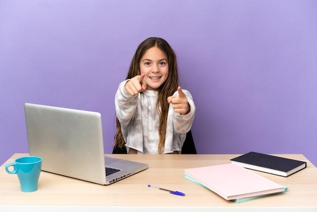 Маленькая студентка на рабочем месте с ноутбуком, изолированным на фиолетовом фоне, удивлена и указывает на фронт