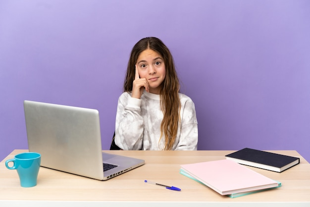Маленькая девочка студента на рабочем месте с ноутбуком, изолированные на фиолетовом фоне, думая об идее