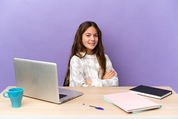 Маленькая студентка на рабочем месте с ноутбуком, изолированные на фиолетовом фоне со скрещенными руками и с нетерпением жду
