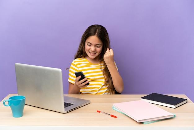 Маленькая девочка студента на рабочем месте с ноутбуком, изолированные на фиолетовом фоне с телефоном в позиции победы