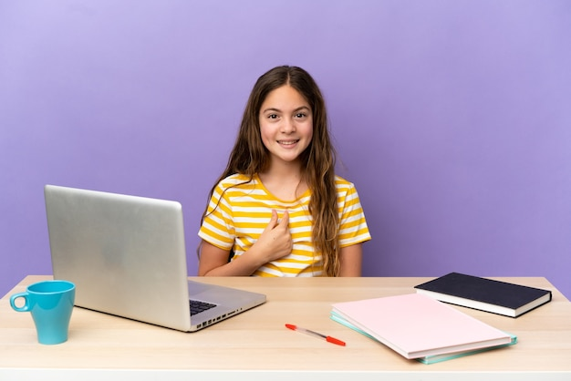Маленькая студентка на рабочем месте с ноутбуком, изолированным на фиолетовом фоне с удивленным выражением лица