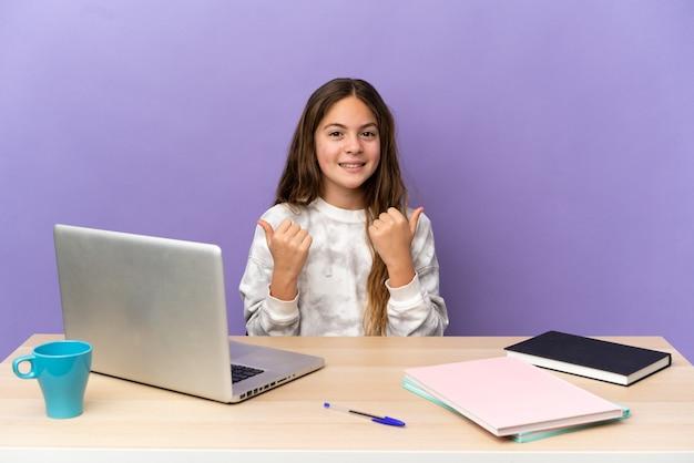 Маленькая девочка-студент на рабочем месте с ноутбуком, изолированным на фиолетовом фоне, с пальцами вверх жестом и улыбкой