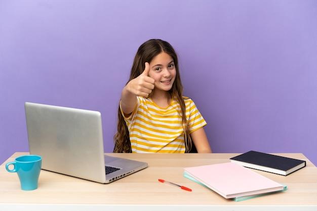 何か良いことが起こったので、親指を立てて紫色の壁にノートパソコンを分離した職場の小さな学生の女の子