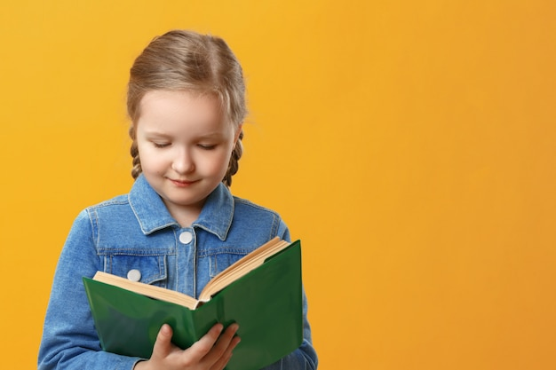 Little student girl is reading a book.