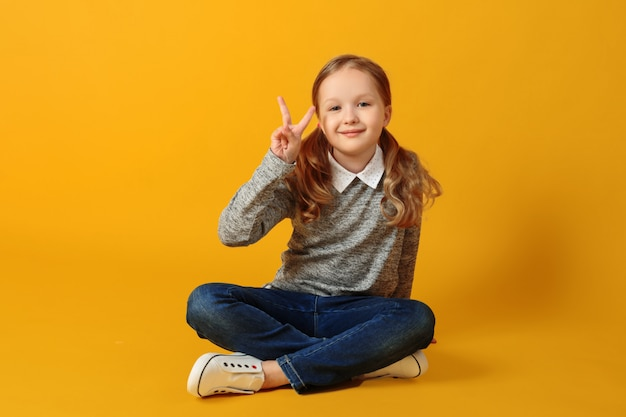 Little student girl is sitting on the floor and showing a victory sign.