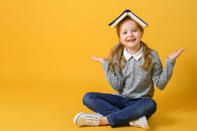 Little student girl is sitting with a book on her head.