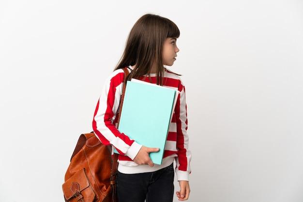 横を見て白い背景で隔離の小さな学生の女の子