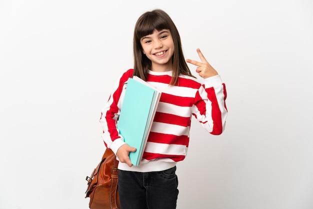 Маленькая девочка студента изолирована на белом фоне улыбается и показывает знак победы