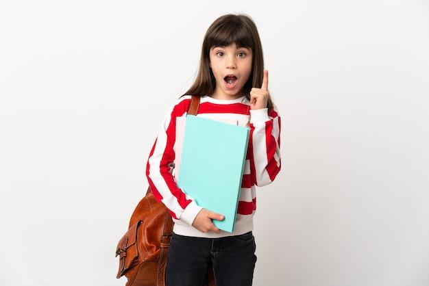 Маленькая девочка студента, изолированные на белом фоне, думая об идее, указывая пальцем вверх