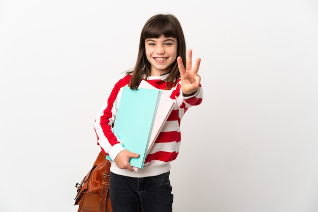 흰 벽에 고립 된 어린 학생 소녀 행복하고 손가락으로 세 세