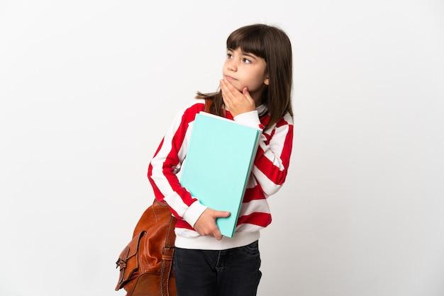 Маленькая девочка студента изолирована на белой стене, глядя вверх, улыбаясь