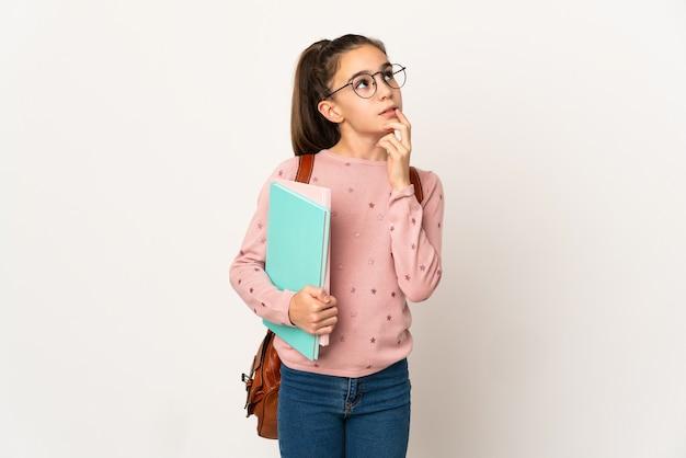 Маленькая девочка студента на изолированном фоне, сомневаясь, глядя вверх