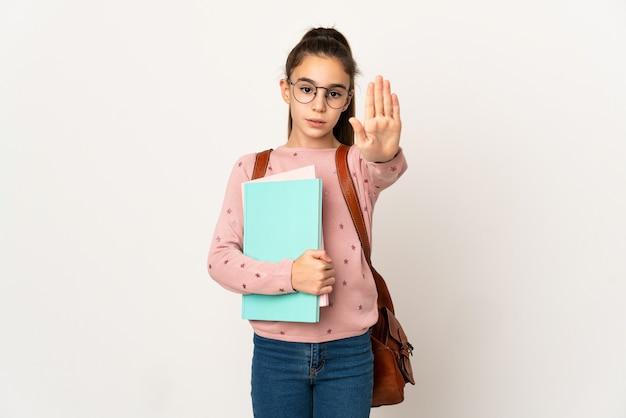 停止ジェスチャーを作る孤立した背景上の小さな学生の女の子