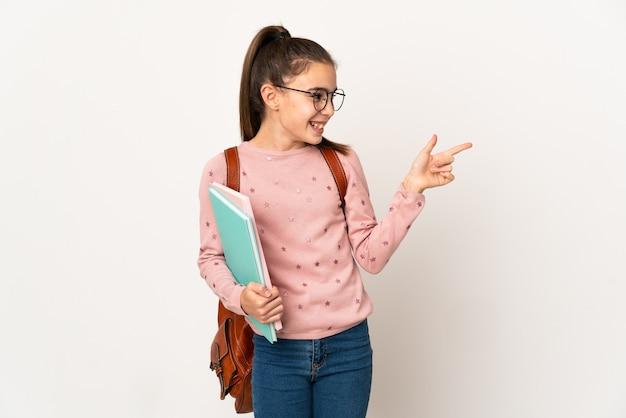 측면에 손가락을 가리키고 제품을 제시하는 격리 된 배경 위에 어린 학생 소녀