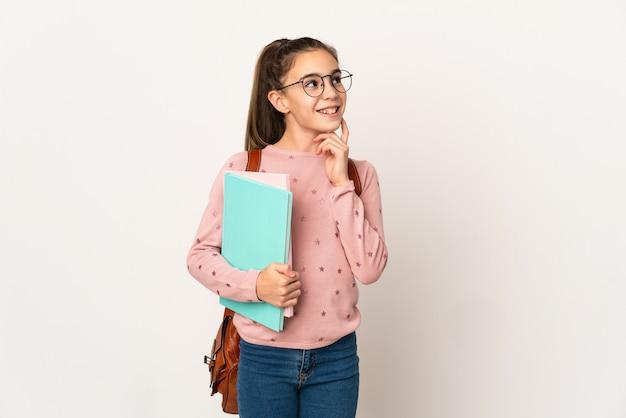 Маленькая девочка студента на изолированном фоне, думая об идее, глядя вверх