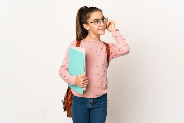 Маленькая девочка студента над изолированной стеной, сомневаясь и думая