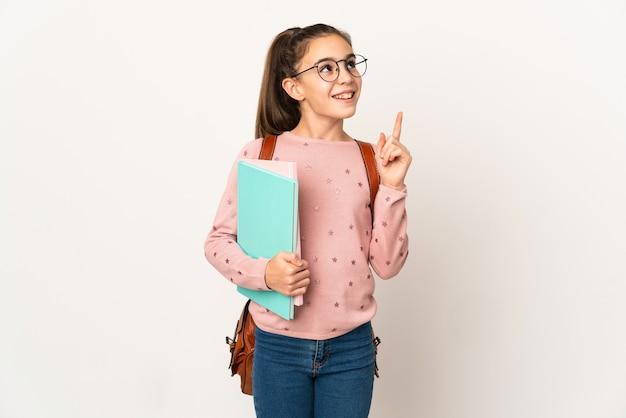 Маленькая студентка над изолированной стеной думает об идее, указывая пальцем вверх