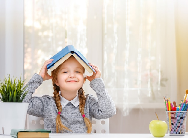 Little student girl sitting at the table with a book on her head and looking into the camera.