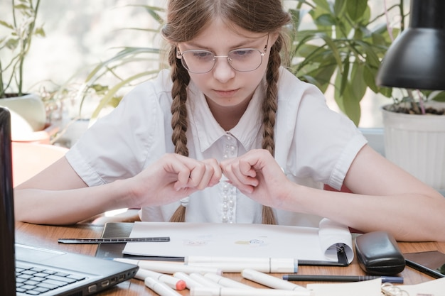 学校で勉強している小さな学生の女の子。ホーム趣味。家で絵を描いている子供の女の子の笑顔。教師から教育を受けるか、両親と一緒に家で学び、勉強するか。宿題をしている少女。