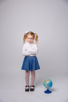 Little student girl with globe of the world on white background