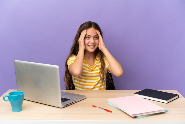 Little student girl in a workplace with a laptop isolated on purple background laughing