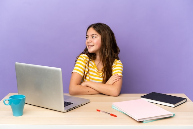 Little student girl in a workplace with a laptop isolated on purple background with arms crossed and happy