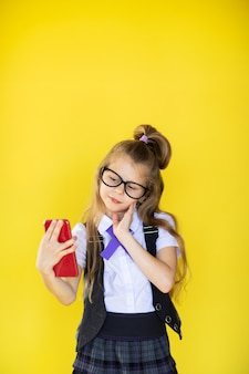 Little student in hipster glasses making selfie on the yellow background