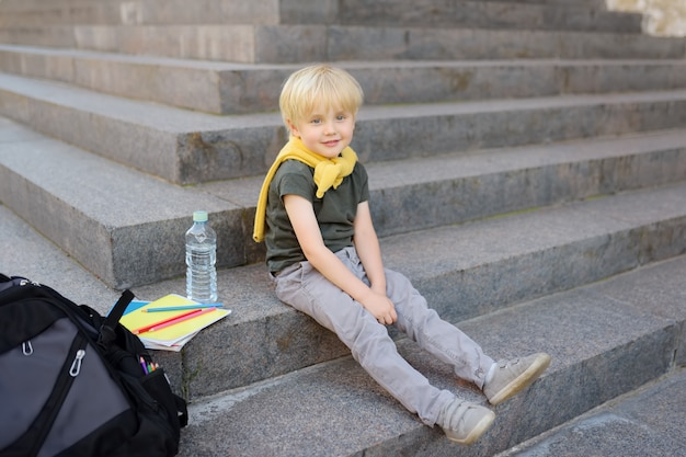 Little student sitting on staircase near the school building.