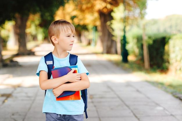 通りでバックパックと本を持っている小さな学生。学校のコンセプトに戻ります。幸せな学童は勉強する準備ができています。屋外で本を持っている賢い男子生徒。勉強する最初の日。