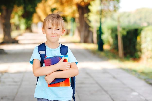 通りでバックパックと本を持っている小さな学生。学校のコンセプトに戻ります。幸せな学童