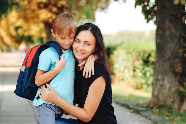 ランドセルを持った小さな生徒が学校の近くで母親を抱きしめます。学校のコンセプトに戻ります。学校に行く途中で母親と一緒に幸せな男子生徒。クラスの初日。