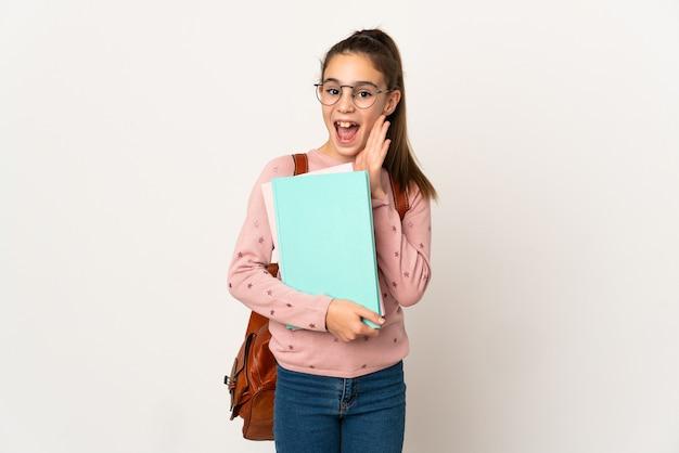 Маленькая студентка над изолированной стеной с удивлением и шокированным выражением лица