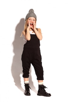 Little stylish girl in dark overall on the white background