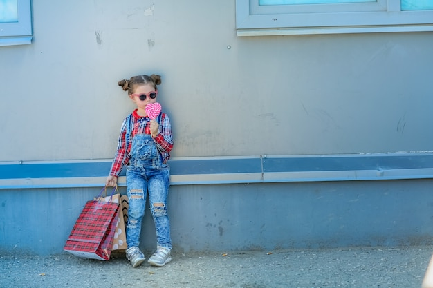 Little stylish girl in sunglasses and two pigtails on her head