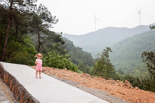 背景の風車のある山の上を歩いてブロンドの髪を持つスタイリッシュな少女。夏の活動、コロナウイルスcovid-19パンデミック中のローカル休暇