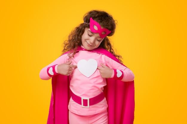 ハートのアイコンを持つ小さなスーパーヒーローの子供の女の子