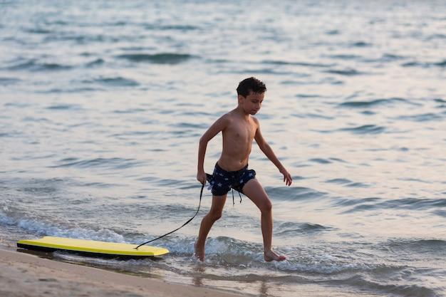 Маленький серфер бежит с бодибордом к морю для катания на волнах