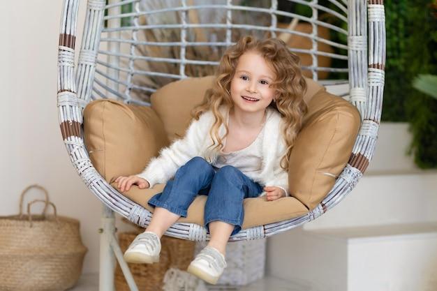 Маленькая удивленная девочка качается на качелях из ротанга в подвесном кресле дома