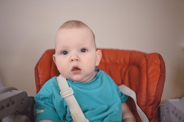 Маленький удивленный новорожденный ребенок сидит на стульчике для кормления