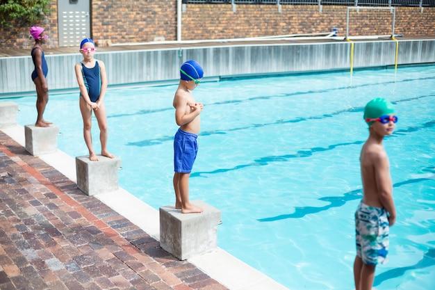 プールサイドのスターティングブロックに立っている小さな水泳選手