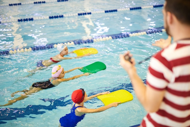 Little swimmers training with instructor