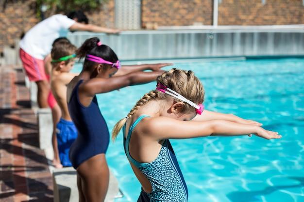 プールに飛び込む準備ができているトレーナーと小さなスイマー